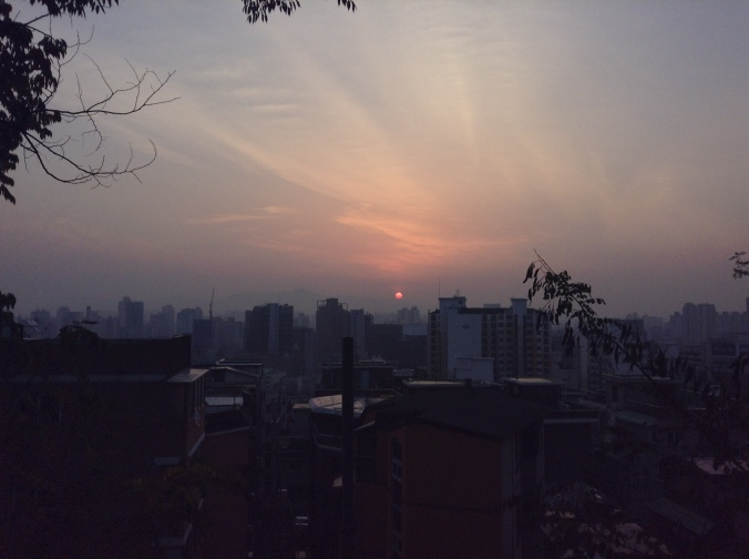 The sun rises over Seoul's mountains and buildings.